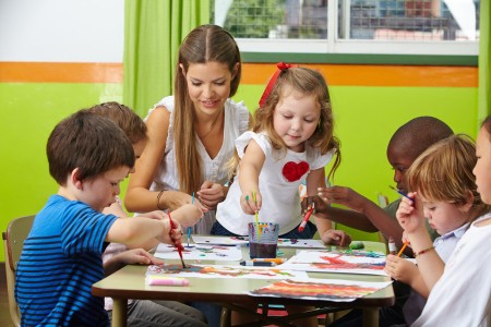 Many children painting together with nursery teacher in a kinder