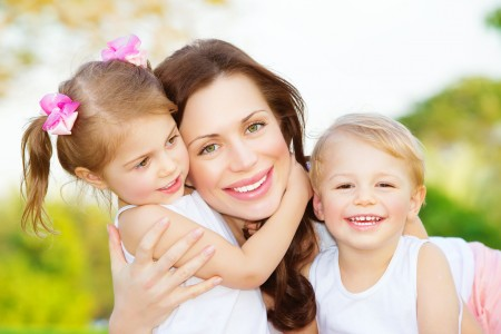 Picture of young mother hugging two little children, closeup por